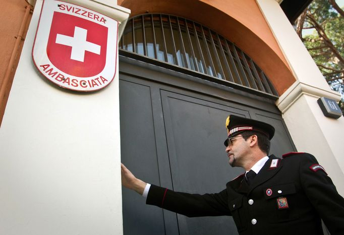 A Carabinieri paramilitary police officer rings the bell at the entrance of the Swiss Embassy in Rome on Thursday, Dec. 23, 2010, where a package exploded and wounded an embassy staffer, police said. (AP Photo/Angelo Carconi)