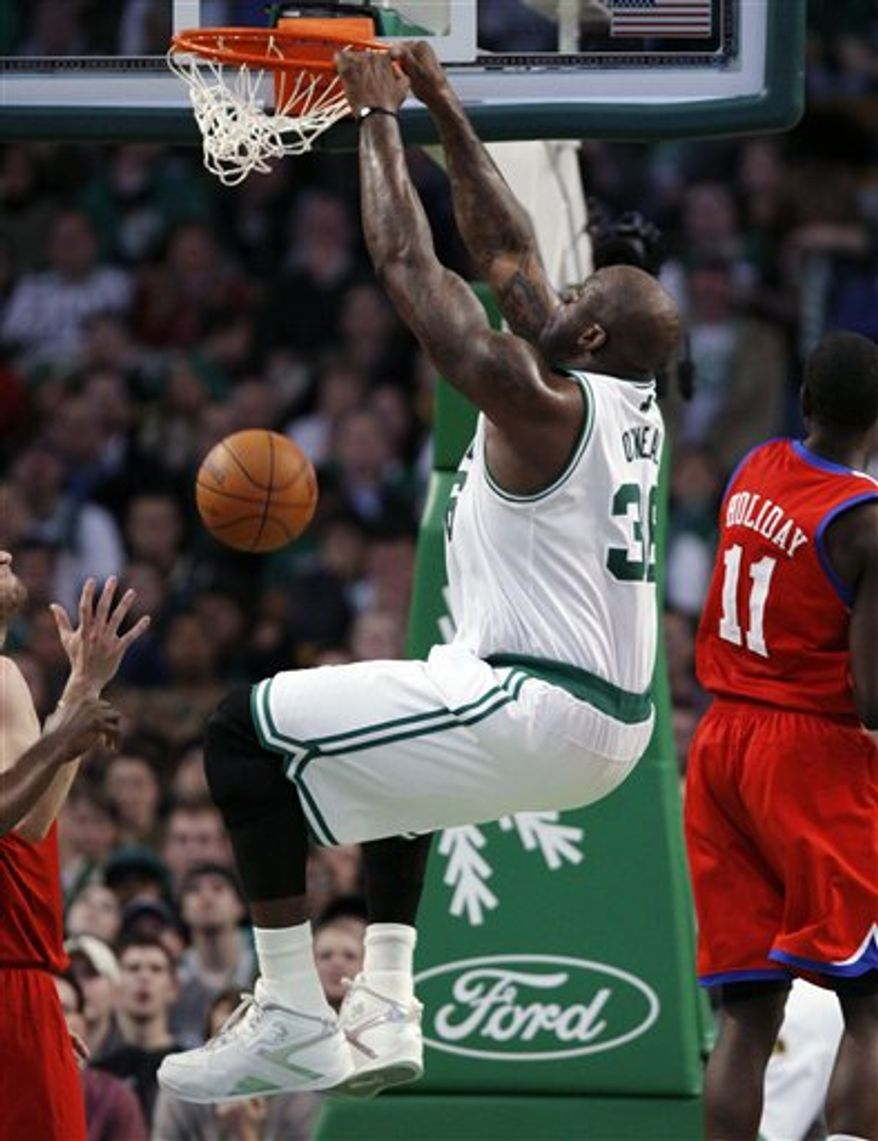 Boston Celtics' Kevin Garnett, top right, blocks a shot by Philadelphia 76ers' Jrue Holiday, top left, in the first quarter of an NBA basketball game, Wednesday, Dec. 22, 2010, in Boston. (AP Photo/Michael Dwyer)