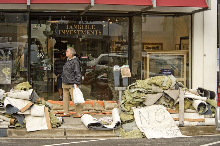 A passer-by walks past water-damaged carpet outside a business on Forest Avenue as Laguna Beach, Calif., cleans up and businesses open downtown on Thursday morning, Dec 23, 2010. (AP Photo/Orange County Register, Ken Steinhardt)
