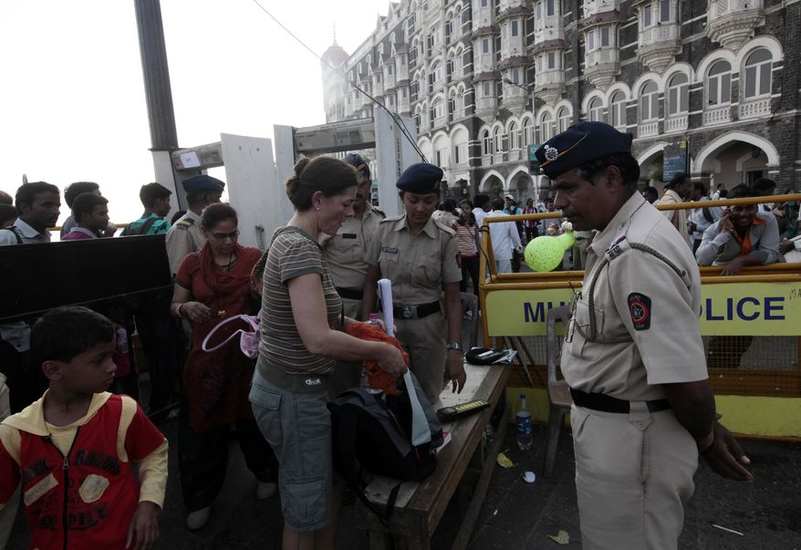 Indian police officials frisk pedestrians outside the Taj Mahal hotel in Mumbai, India, on Friday, Dec. 24, 2010. Police searched India's financial capital on Friday for four men who authorities believe entered Mumbai to carry out a terrorist attack, a top police official said. (AP Photo/Rajanish Kakade).