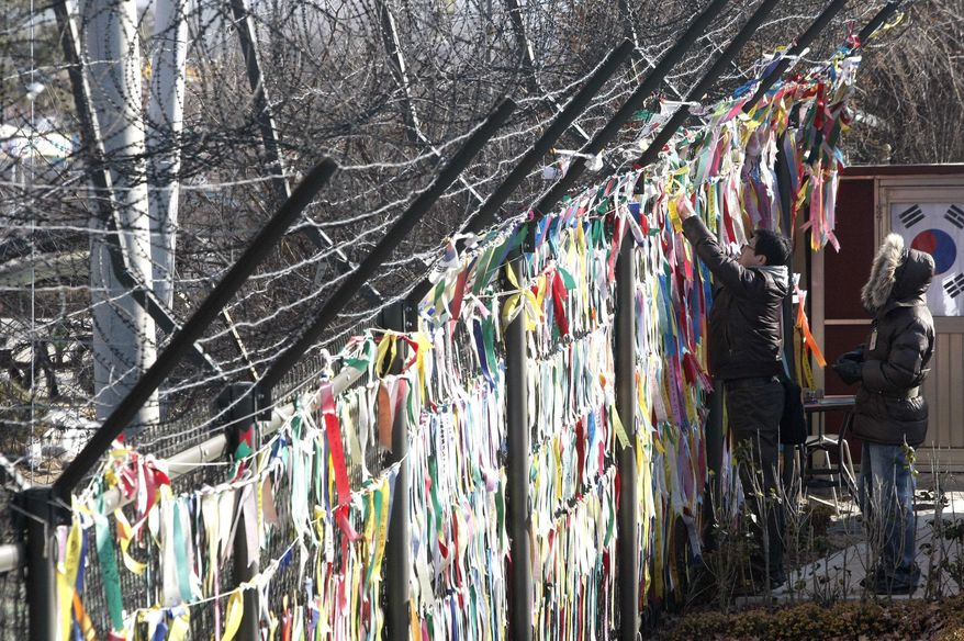 A tourist hangs on a ribbon with messages wishing for reunification of the two Koreas at a barbed-wire fence at the at the Imjingak Pavilion near the border village of Panmunjom in Paju, South Korea, on Friday, Dec. 24, 2010. (AP Photo/Ahn Young-joon)