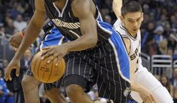 Orlando Magic forward Brandon Bass (30) grabs a defensive rebound over San Antonio Spurs center Tim Duncan (21) as Magic's Hedo Turkoglu, left, of Turkey, and Jason Richardson, right, watch during the first half of an NBA basketball game in Orlando, Fla., Thursday, Dec. 23, 2010. (AP Photo/Phelan M. Ebenhack)