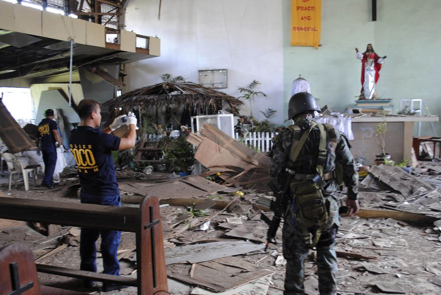 Philippine National Police investigators inspect the damage at the Sacred Heart Catholic Chapel following an explosion during a Christmas Day Mass on Saturday, Dec. 25, 2010, on the volatile island of Jolo, Sulu province, in the southern Philippines. (AP Photo/Nickee Butlangan)