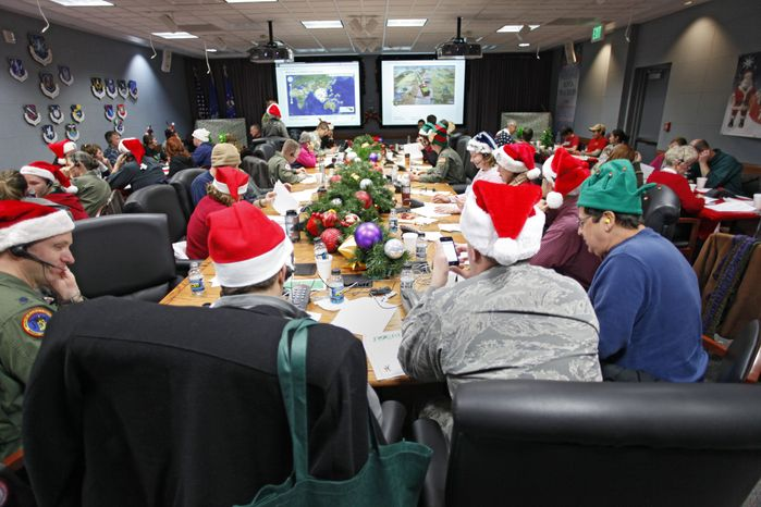 Volunteers take phone calls and answer e-mails at the Santa Tracking Operations Center at Peterson Air Force Base near Colorado Springs, Colo., on Friday, Dec. 24, 2010. Tracking Santa's travels is a celebrated tradition at the North American Aerospace Defense Command (NORAD), and it unfolded Friday for the 55th year. (AP Photo/Ed Andrieski)