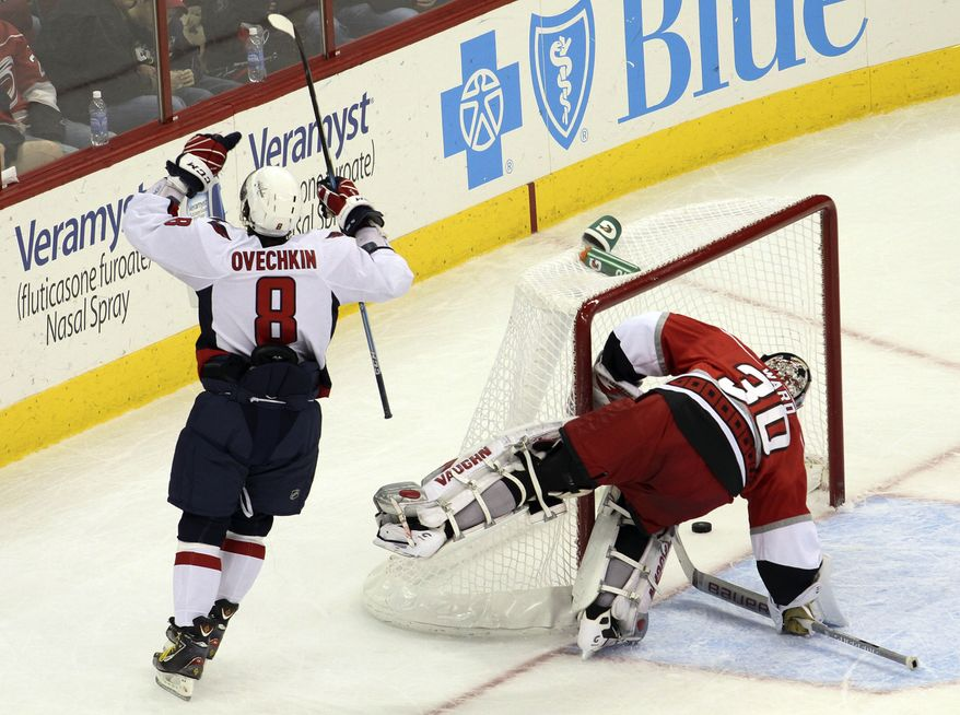 Washington Capitals left wing Alex Ovechkin (8) celebrates a goal against Carolina Hurricanes goalie Cam Ward (30) during the second period of an NHL hockey game in Raleigh, N.C., Sunday, Dec. 26, 2010. (AP Photo/Jim R. Bounds)