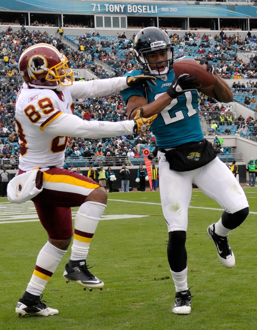 Jacksonville Jaguars cornerback Derek Cox (21), right, intercepts a pass in the end zone in front of Washington Redskins wide receiver Santana Moss (89) during the first half of an NFL football game in Jacksonville, Fla., Sunday, Dec. 26, 2010.(AP Photo/Phelan M. Ebenhack)