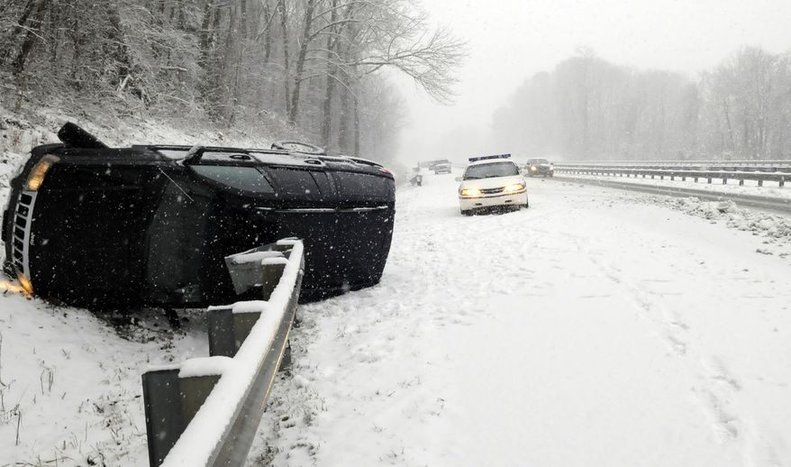 An overturned SUV lies in a snowy ditch along I-40 in western North Carolina at Mile Marker 48 on Saturday, Dec. 25, 2010. Much of North Carolina was under a winter storm warning. (AP Photo/The Asheville Citizen-Times, Margaret Hester)