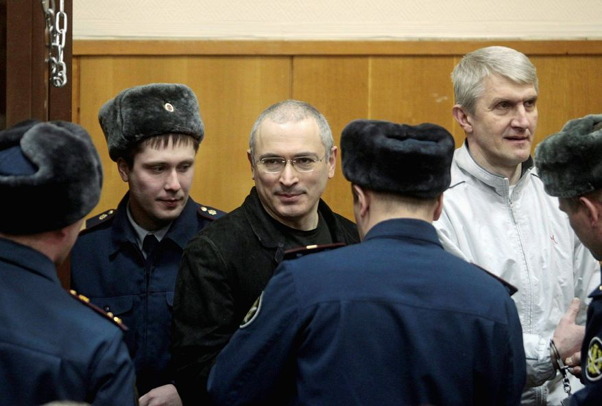 ASSOCIATED PRESS Mikhail Khodorkovsky (center) and co-defendant Platon Lebedev (right) are escorted to a courtroom in Moscow on Monday. A judge declared Khodorkovsky, a former oil tycoon, guilty of theft and money laundering.
