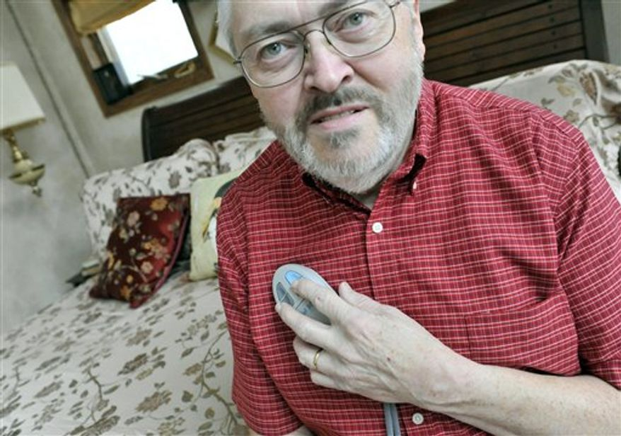 Rik Krohn displays the remote control unit he uses to turn on an experimental nerve stimulator to combat his sleep apnea, Tuesday, Dec. 21, 2010, at his home in Burnsville, Minn. Loud snoring may do more than irritate your spouse: It can signal sleep apnea, depriving you of enough zzzz's to trigger a car crash, even a heart attack. Now scientists are testing if an implanted device might help, keeping sufferers' airways open by zapping the tongue during sleep. (AP Photo/Jim Mone)