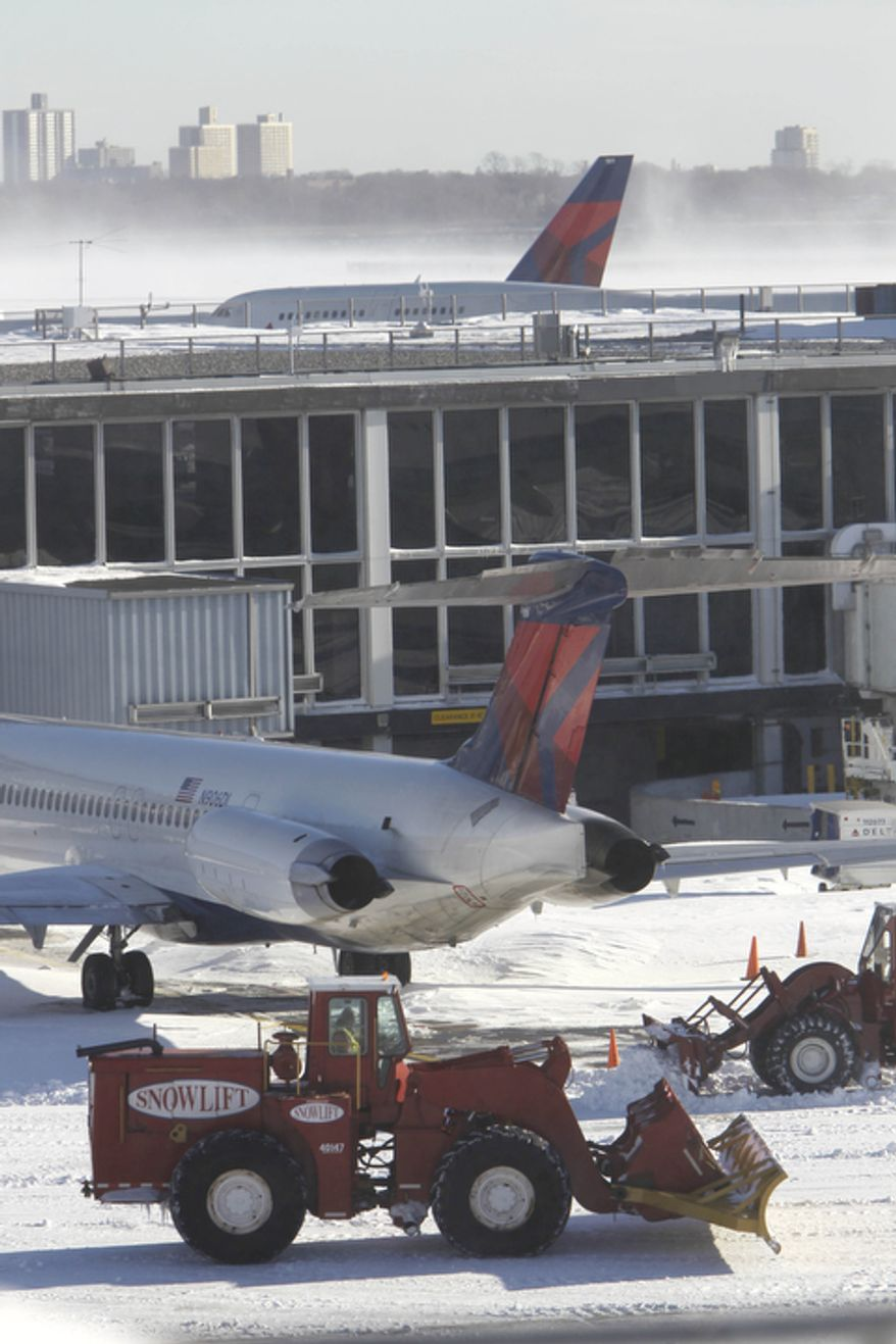 Snow removal continues at John F. Kennedy International Airport.  (AP Photo/Seth Wenig)