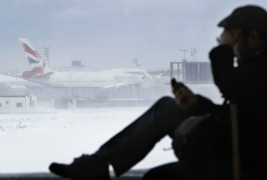 Kevin Fagan, from San Francisco, talks on his phone while an airplane sits motionless on the runway at John F. Kennedy International Airport in New York, Monday, Dec. 27, 2010. (AP Photo/Seth Wenig)