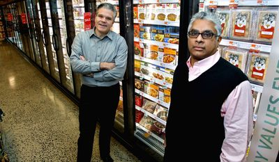 Jack Acree, executive vice president with American Halal Co. Inc. (left), and Adnan Durrani, his chief halal officer, display their products at a Whole Foods store in Darien, Conn. The company helped Whole Foods develop its first nationally distributed halal food product, called Saffron Road entrees. (Associated Press)
