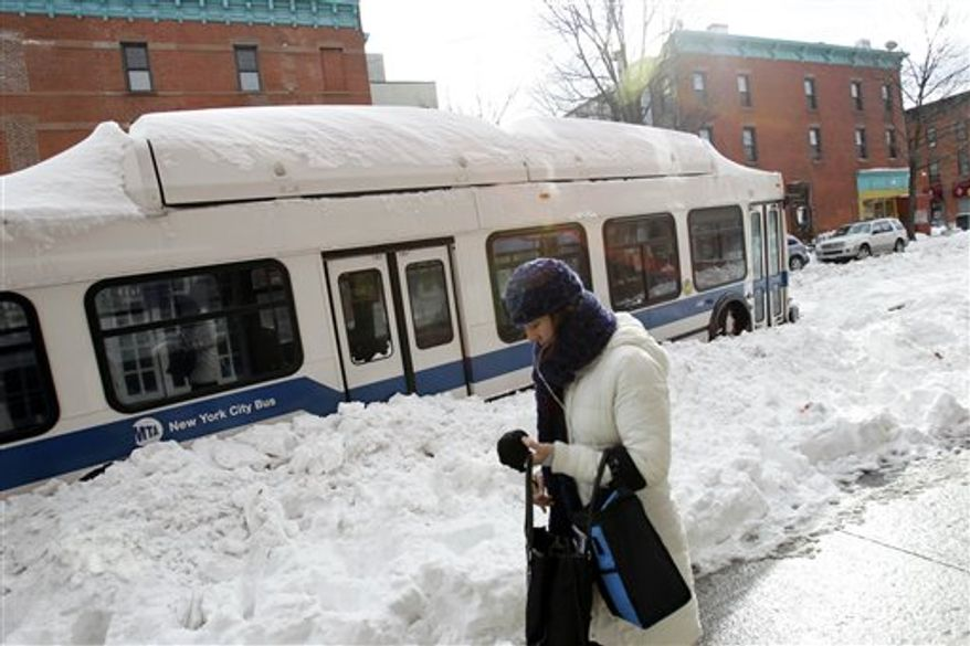 A woman walks past a New York City bus stuck in the snow in the Brooklyn borough of New York, Tuesday, Dec. 28, 2010. (AP Photo/Seth Wenig)