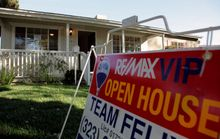 """An """"open house"""" sign is seen on the front lawn of a home for sale in Los Angeles. Home prices are dropping in the nation's largest cities and are expected to fall through next year, with the worst declines coming in areas with high numbers of foreclosures. (Associated Press)"""