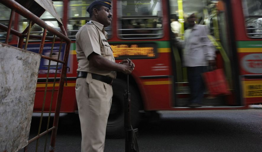 A policeman stands guard as a city bus passes by in Mumbai, India, Tuesday, Dec. 28, 2010. India's Home Ministry has issued a countrywide alert after receiving information of a potential terror strike by a Pakistan-based militant group, an official said Tuesday. (AP Photo/Rajanish Kakade)