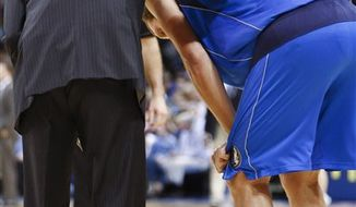 Dallas Mavericks forward Dirk Nowitzki, right, stands with a trainer after getting hurt during the second quarter of an NBA basketball game against the Oklahoma City Thunder in Oklahoma City, Monday, Dec. 27, 2010. (AP Photo/Alonzo Adams)