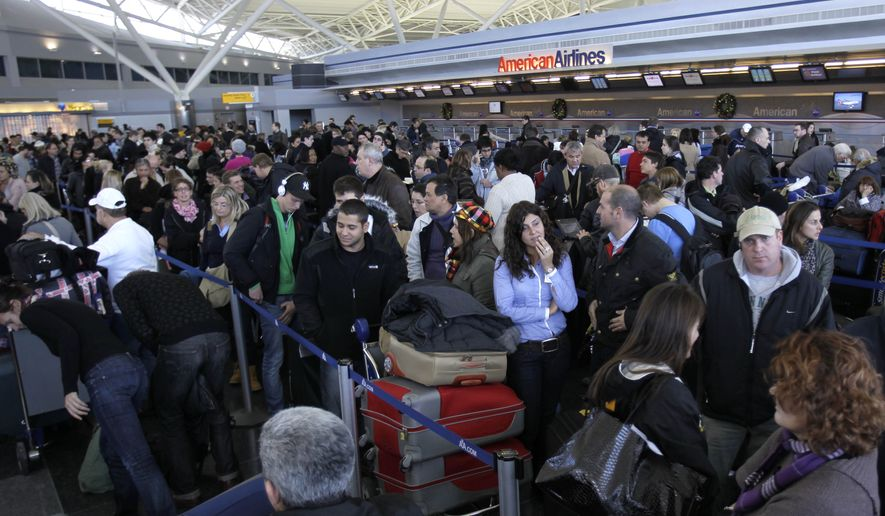 Travelers wait in line to find out the status of their flights at John F. Kennedy International Airport in New York on Monday, Dec. 27, 2010. (AP Photo/Seth Wenig)