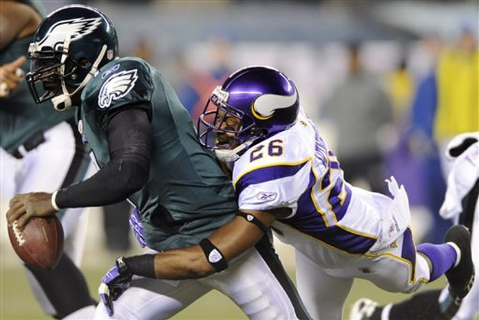 Philadelphia Eagles' Michael Vick, left, is tackled by Minnesota Vikings' Antoine Winfield in the first half of an NFL foot