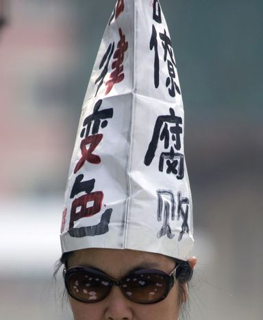 "**FILE** A Chinese petitioner wears a hat with the words ""Officials Corrupt, Changed Judiciary"" in Beijing on May 4, 2009. China plans to crack down in the coming year on lavish parties and seminars organized by government officials, hoping to placate a public angered by corruption and accounts of sex and booze-fueled fetes held at taxpayer expense. (Associated Press)"