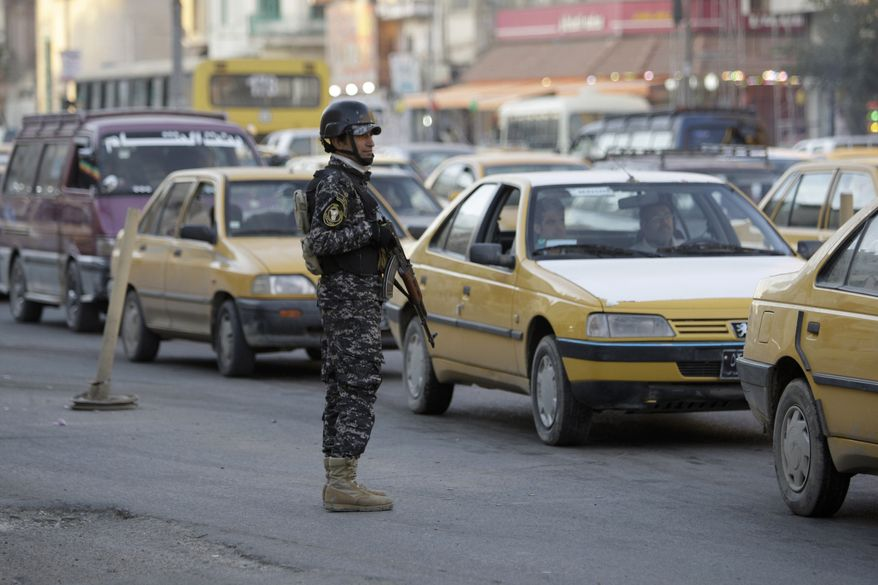 An Iraqi policeman stands guard while hundreds of vehicles line up to be searched at a checkpoint in Baghdad on Tuesday, Dec. 28, 2010. Security officials are investigating the possibility of removing some of the hundreds of checkpoints across the city in a sign of the improving security situation. The checkpoints are designed to catch insurgents, but they also slow traffic in the already congested city. (AP Photo/Hadi Mizban)