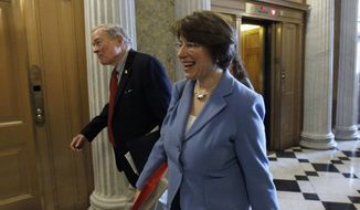 ** FILE ** Sen. Christopher Bond, D-Mo., left, and Sen. Amy Klobuchar, D-Minn., walk near the floor of the Senate during an unusual Saturday session on Capitol Hill in Washington on Saturday, Dec. 18, 2010. (AP Photo/Alex Brandon)