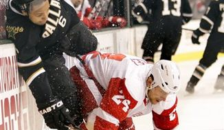 Dallas Stars defenseman Trevor Daley (6) is hit into the boards by Detroit Red Wings defenseman Ruslan Salei (24), of Belarus,  during the first period of an NHL hockey game Wednesday Dec. 29, 2010, in Dallas. (AP Photo/Mike Fuentes)