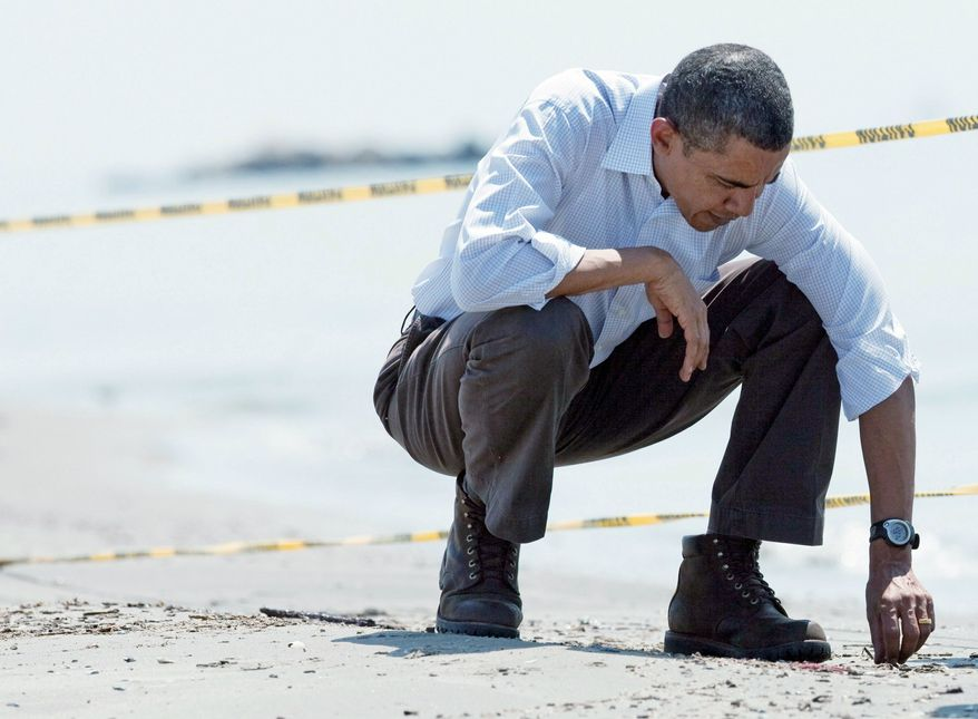 "President Obama picks up a ""tar ball"" from the beach in Port Fourchon, La., in May after the largest oil spill in U.S. history in the Gulf of Mexico. (Associated Press)"