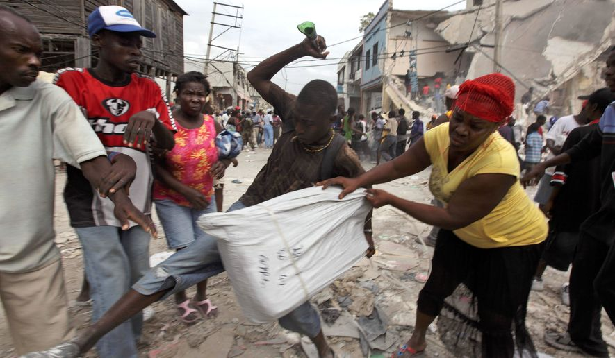 KEY EVENTS: A looter in Port-au-Prince, Haiti, fends off rivals a week after the Jan. 12 earthquake in that impoverished country. (Associated Press)