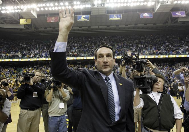 Duke coach Mike Krzyzewski waves to the crowd after Duke's 108-62 win over North Carolina-Greensboro on Wednesday in Greensboro, N.C. Krzyzewski moved past longtime rival Dean Smith into second place on the men's all-time wins list. (Associated Press)