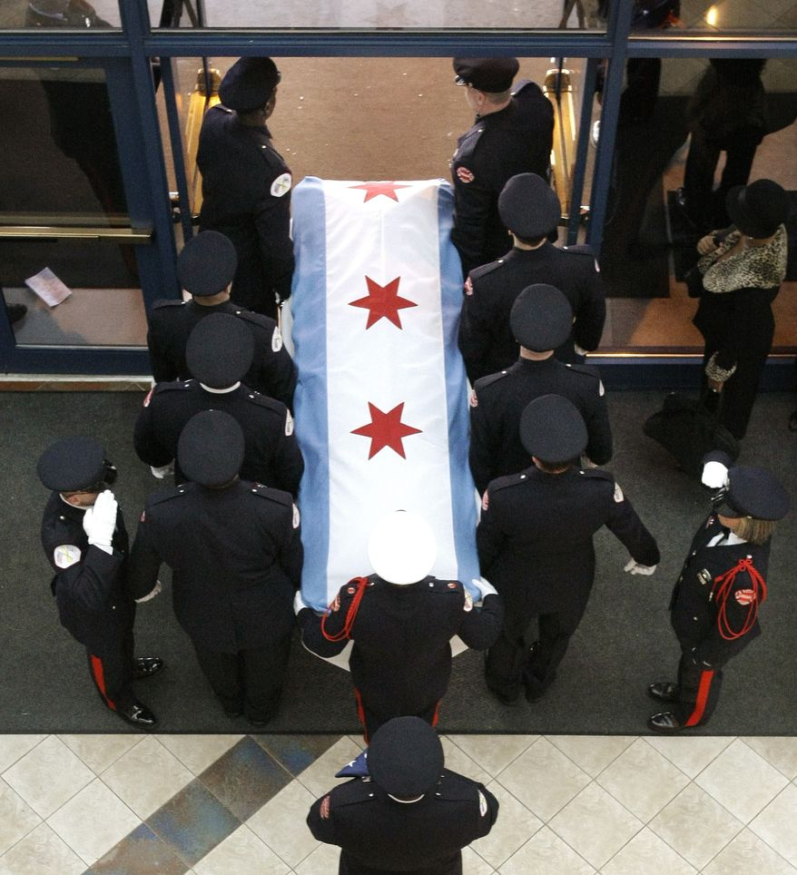 Chicago firefighters carry the casket containing the body of firefighter Corey Ankum to a fire truck after Dec. 30 funeral services in Chicago. Ankum was one of two firefighters killed last week when a roof collapsed after a fire. (Associated Press)