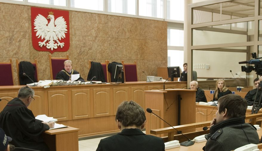 """Anders Hogstrom (right) of Sweden listens during a court session in Krakow, Poland, on Thursday, Dec. 30, 2010. Judge Jaroslaw Gaberle sentenced Hogstrom to two years and eight months in prison for instigating the theft a year ago of the infamous """"Arbeit Macht Frei"""" (""""Work Sets You Free"""") sign from the Auschwitz death camp memorial. (AP Photo/Jerzy Rucinski)"""
