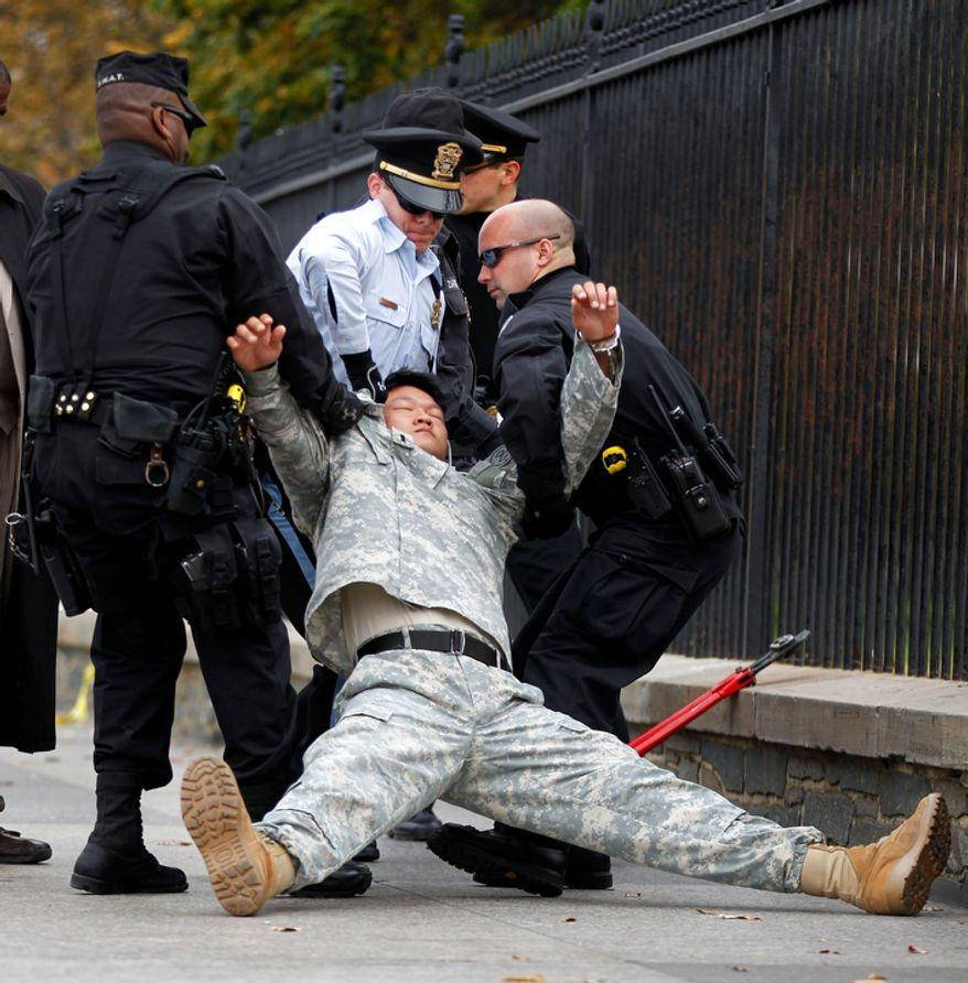 "** FILE ** Dan Choi (center) falls as he is arrested for handcuffing himself to the fence outside the White House in Washington during a protest against the military's ""don't ask, don't tell"" policy on Nov. 15, 2010. (AP Photo/Pablo Martinez Monsivais, File)"