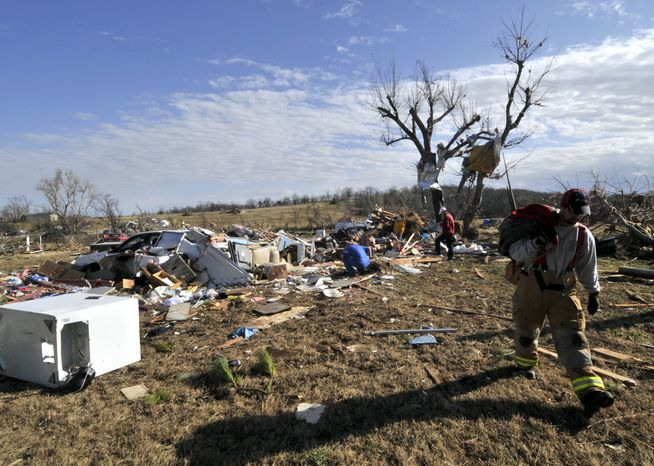 An unidentified rescue worker walks past debris after a tornado tore through Cincinnati, Ark., early in the morning on Friday, Dec. 31, 2010. A tornado fueled by an unusually warm winter air sliced through parts of the South and Midwest early on New Year's Eve, killing six people, injuring several others and knocking out power to thousands of homes and businesses. (AP Photo/April L. Brown)