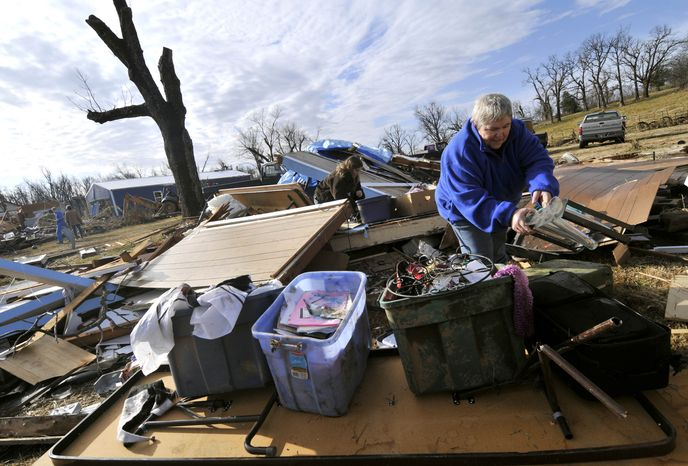 Margie Sisemore cleans up in the after a tornado destroyed several homes in the small town of Cincinnati, Ark., in western Washington County early in the morning on Friday, Dec. 31, 2010. A tornado fueled by an unusually warm winter air sliced through parts of the South and Midwest early on New Year's Eve, killing six people, injuring several others and knocking out power to thousands of homes and businesses. (AP Photo/April L. Brown)