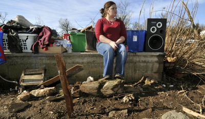 Paige Sisemore, 18, of Lincoln, Ark., sits on the foundation of a home behind a makeshift cross made from debris after a tornado tore through the small town of Cincinnati, Ark., on Friday, Dec. 31, 2010. A tornado fueled by an unusually warm winter air sliced through parts of the South and Midwest early on New Year's Eve, killing six people, injuring several others and knocking out power to thousands of homes and businesses. (AP Photo/April L. Brown)