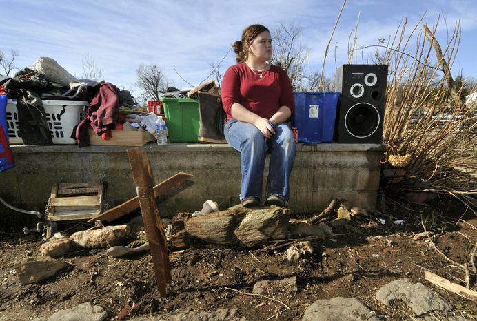 Paige Sisemore, 18, of Lincoln, Ark., sits on the foundation of a home behind a makeshift cross made from debris after a tornado tore through the small town of Cincinnati, Ark., on Friday, Dec. 31, 2010. A tornado fueled by an unusually warm winter air sliced through parts of the South and Midwest early on New Year&am