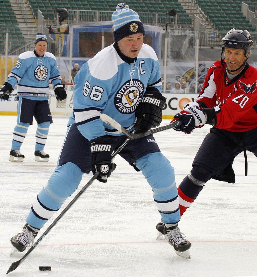 Pittsburgh Penguins alumnus Mario Lemieux (66) is guarded by Washington Capitals alumnus Michal Pivonka (20) during an exhibition NHL hockey game between alumni of the two teams on an outdoor rink at Heinz Field in Pittsburgh, Friday, Dec. 31, 2010. The game ended tied at 5-5. (AP Photo/Gene J. Puskar)