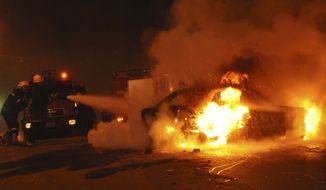 ** FILE ** Firemen try to put out a vehicle blaze following a car bombing in front of a Coptic Christian church in Alexandria, Egypt, early on Saturday, Jan. 1, 2011. The car exploded in front of the church as worshippers emerged from a New Year's Mass in the Mediterranean port city, killing at least seven people, officials said. (AP Photo)