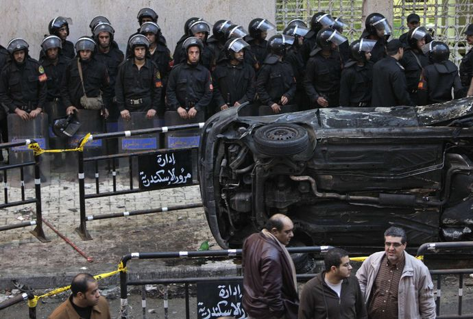 Egyptian riot police form a line behind an upturned and burnt car outside the Coptic Christian Saints Church, unseen, in the Mediterranean port city of Alexandria, Egypt, on Saturday, Jan. 1, 2011. A car exploded in front of the church early Saturday as worshippers emerged from a New Year's Mass, killing at least 21 people according to officials. (AP Photo/Ben Curtis)