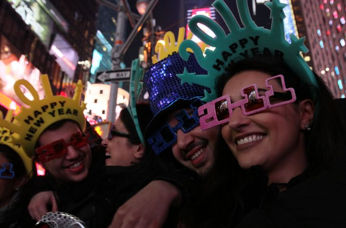 A group of friends pose for photographs as they take part in the New Year's Eve festivities in New York's Times Square on Friday, Dec. 31, 2010. (AP Photo/Tina Fineberg)