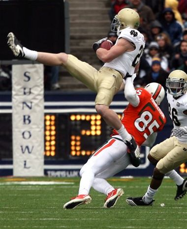 Notre Dame wide receiver Theo Riddick, right, evades Miami tackler Vaughn Telemaque during the Sun Bowl NCAA college football game on Friday, Dec. 31, 2010, in El Paso, Texas. (AP Photo/El Paso Times, Mark Lambie)