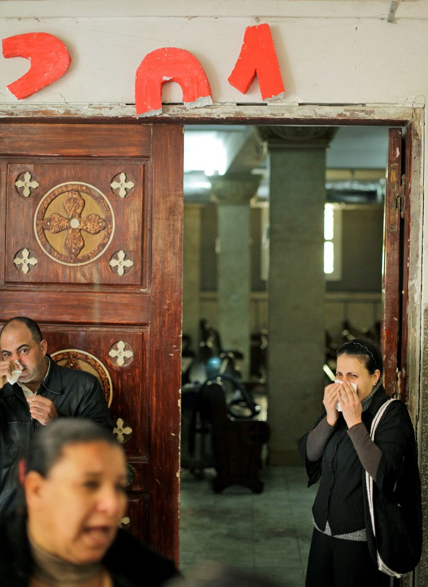 """Coptic Christians weep under the broken remains of a sign celebrating """"2011"""" Sunday in the blood-spattered Saints Church in Alexandria, Egypt. Just after a New Year's Mass, 21 worshippers were killed and about 100 wounded in an apparent suicide bombing. (Associated Press)"""