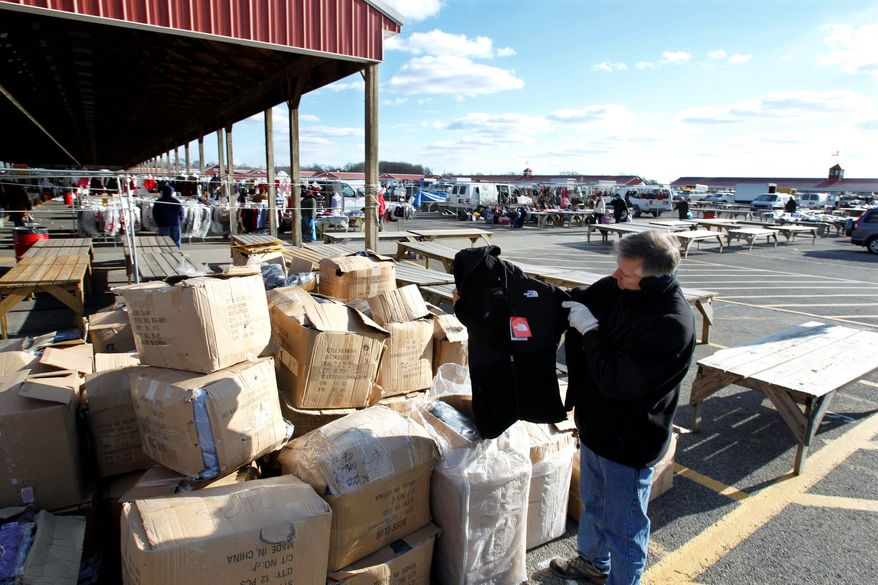 New Jersey State Police Lt. Michael E. McDonnell finds a counterfeit North Face coat among boxes full of fake name-brand clothing that police seized last month from a vendor at a flea market. (Associated Press)