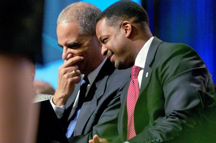 Washington D.C. Council Chairman-Elect Kwame Brown, right, confers with U.S. Attorney General Eric Holder during the inauguration of Vincent C. Gray. (Rod Lamkey Jr / for The Washington Times)