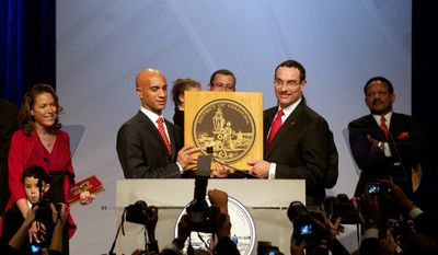 Vincent C. Gray, right, joins Adrian Fenty, left, at the podium following Vincent C. Gray's taking of the oath of office as the new mayor of Washington D.C. on Sunday, January 2, 2011.  (Rod Lamkey Jr / for The Washington Times)