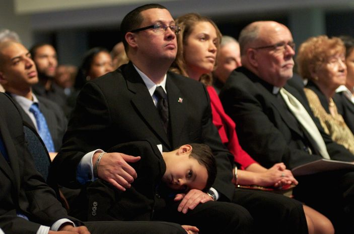 D.C. Mayor Vincent C. Gray's grandson, Austin, 5, rests on the lap of his father, Stacy Tucker, as the new mayor delivers his inauguration speech on Sunday. Mr. Gray, a native of D.C., is the sixth elected mayor of the District, and he succeeds Mayor Adrian M. Fenty. (Rod Lamkey Jr./Special to The Washington Times)