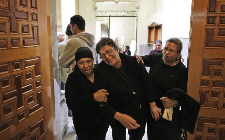 Ahlam Fawzy Saber (center), an Egyptian Coptic Christian who lost two of her sisters and a niece in an apparent suicide bombing during midnight Mass, is helped back into the Saints Church in Alexandria, Egypt, after collapsing from emotion following morning Mass on Sunday, Jan. 2, 2011. Grieving Christians, many clad in black, were back praying Sunday in the blood-spattered church, where 21 worshippers were killed in the blast. (AP Photo/Ben Curtis) ** FILE **