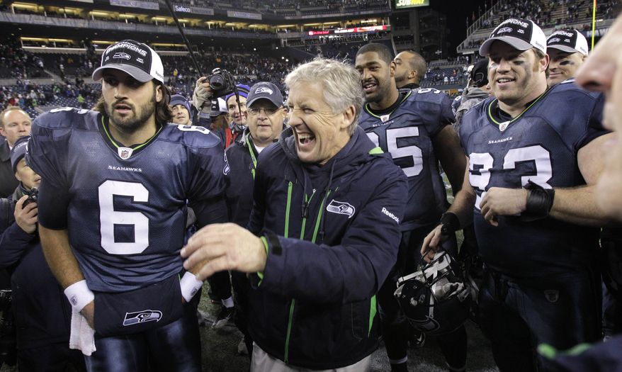 Seattle Seahawks coach Pete Carroll, center, smiles as he huddles with the team after they beat the St. Louis Rams in an NFL football game, Sunday, Jan. 2, 2011, in Seattle. The Seahawks won 16-6 winning its first division title since 2007. (AP Photo/Elaine Thompson)