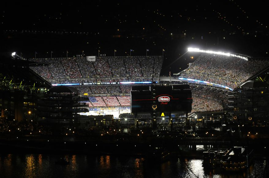 Fans create an American flag during the national anthem at Heinz Field in Pittsburgh before the NHL Winter Classic hockey game between the Pittsburgh Penguins and the Washington Capitals on Saturday, Jan. 1, 2011. (AP Photo/Pittsburgh Tribune-Review, Justin Merriman)