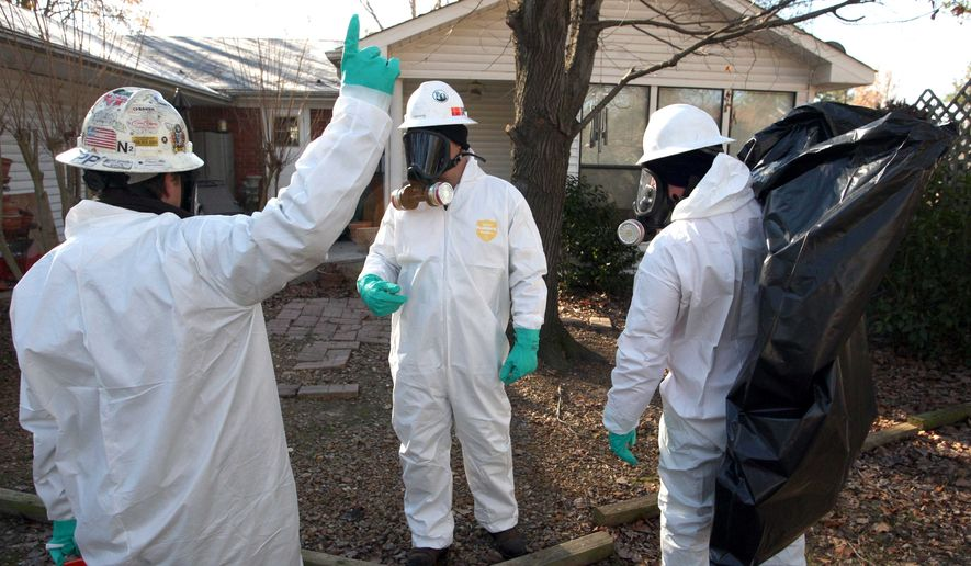 Workers with United States Environmental Services LLC collect dead birds from the back yard of a home in Beebe, Ark. Sunday, Jan. 2, 2011. Wildlife officials are trying to determine what caused more than 3,000 blackbirds to die and fall from the sky over the Arkansas town. (AP Photo/The Arkansas Democrat-Gazette, Stephen B. Thornton)